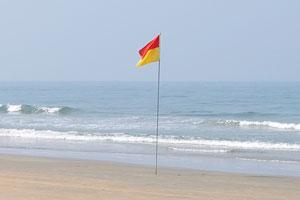 Пляж Кавелоссим: красно-жёлтый флаг означает, что нет никакой опасности для плавания