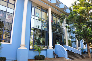 Большое синие здание с полицейским у входа