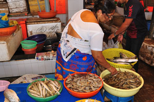 Рыбный рынок: женщина продаёт креветки