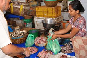 Рыбный рынок: мужчина покупает мелкую рыбу