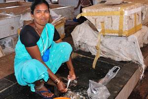 Рыбный рынок: женщина чистит рыбу