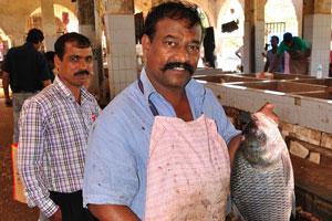 Рыбный рынок: мужчина с большой рыбой и большим ножом в руках