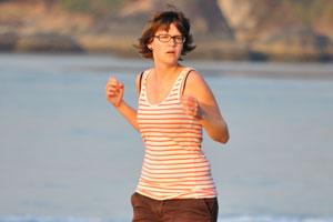 Женщина, бегущая утром по пляжу