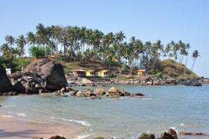 Скалы и кокосовые пальмы на южной оконечности пляжа