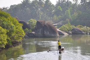 Индийский мужчина плывёт на тонкой лодке с помощью длинного шеста