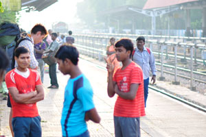 Утомленный турист с рюкзаком ждёт поезда