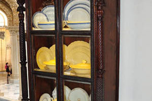 Стеклянный шкаф с посудой жёлтого цвета