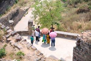 Индийские путешественники с открытыми зонтиками от солнца