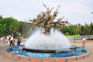 Дерево с золотыми листьями внутри фонтана водяного тумана