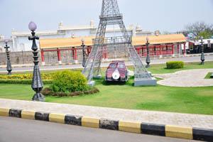 Игрушечный автомобиль под статуей Эйфелевой башни