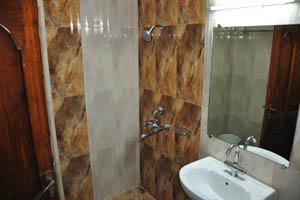 Отель Mandakini Jaya International, умывальник и душ в ванной