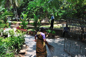 Женщина подметает аллею у входа в Вели