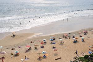 Вечером перед закатом на пляже Варкала установлено много зонтиков