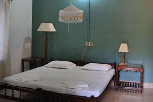 Двуспальная кровать в комнате с видом на сад - дом отдыха «Эдемский сад»