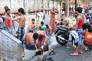 Люди принимают водные процедуры на улице