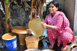 Женщина в нарядном платье моет посуду под банановыми деревьями