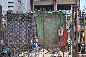 Бедные люди вывешивают старую одежду на заборе