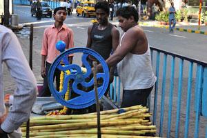 Продавцы свежевыжатого сока из сахарного тростника на улице Камак в Калькутте