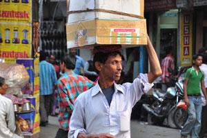 Мужчина несёт большую коробку на своей голове