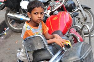 Мальчик рядом с красным мотоциклом Ройял Энфилд