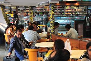 Молодые индийцы сидят за столами кафе Халдирам Бхуджиавала