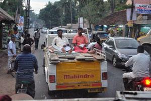 Двое мужчин медитируют (шутка) сидя в кузове грузовика Махиндра на пути в Тривандрум