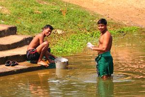 Молодые парни стирают свою одежду в пруду