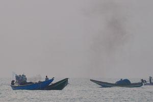 Дым от дизельного топлива поднимается над лодками рыбаков