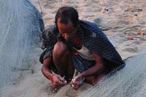 Индийский рыбак чинит рыболовную сеть