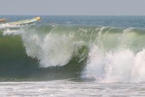 Океанская волна с шумом падает на берег