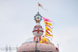 Жёлтые и красные флаги развеваются над храмом