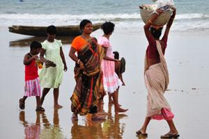 Женщина несёт рыбу в тазу на своей голове