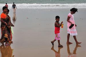 Индийская семья гуляет на берегу океана