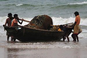 Рыбаки тянут лодку с сетями из океана