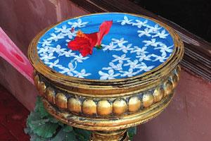 Лепестки цветов плавают на поверхности воды в вазе