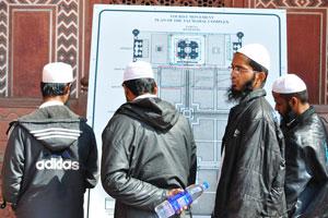 Четыре мусульманина в чёрных куртках и белых шапочках изучают план Тадж-Махала